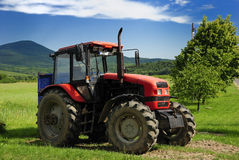 Red tractor. With blue trailer on a grass field Stock Photography