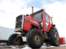 Red tractor. Low perspective of a red tractor used to remove snow. Some indutrial environment can be seen Stock Photography