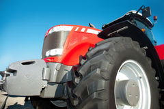 Red tractor against the clear blue sky. Close-up Royalty Free Stock Photography