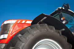 Red tractor against the clear blue sky. Close-up Stock Photos