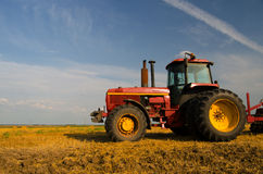 Red tractor on the agricultural field Stock Photos