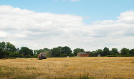 Red tractor baling straw in a farm field Stock Photography