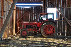 Red tractor in barn. Red old tractor in old barn stock photography
