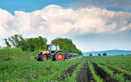 Red tractor cultivating field under blue sky royalty free stock photo