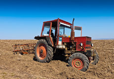 Red tractor. Cultivation of an old red tractor on farm level Stock Images
