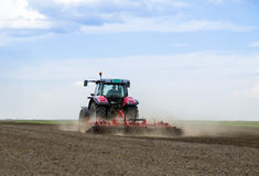 Red tractor driven by farmer cultivating land Royalty Free Stock Photography