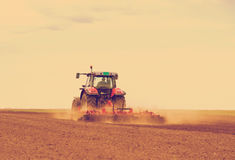 Red tractor driven by farmer cultivating land at spring. Stock Image