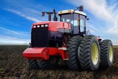 Red tractor on field. Closeup of modern red tractor on field with blue sky and cloudscape background Stock Photo