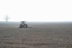 A red tractor on a field. A farmer harrowing a misty field Stock Photo