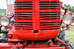 Red tractor grille. Close-up of the grille of a shiny red tractor stock image