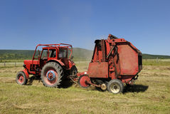Red tractor and hay baler Stock Photos
