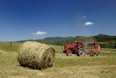 Red tractor and hay baler Royalty Free Stock Photo