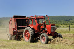 A red tractor and hay baler. Circular hay baler and red tractor royalty free stock photography