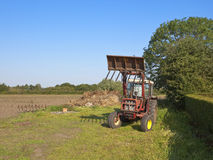 Red tractor and manure heap Stock Image