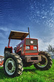 Red tractor on the meadow Stock Photo