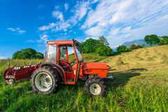 Red tractor in a mountain meadow. With hay bales handmade Royalty Free Stock Image