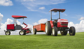Red tractor and mowers with trailer. On a grass field Stock Image