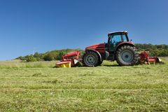 Red tractor mowing the meadow Royalty Free Stock Photos
