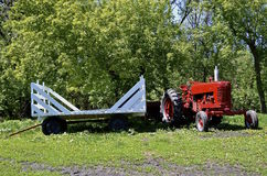 Red tractor parked behind a white hay rack Royalty Free Stock Photos