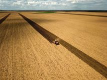 Red tractor plow the field. Air view Royalty Free Stock Image