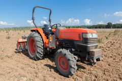 Red tractor with plow in field. Stock Photos