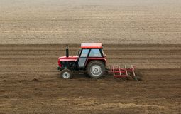 Red tractor in a plowed field Stock Image