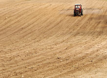 Red tractor on plowed field Stock Photo