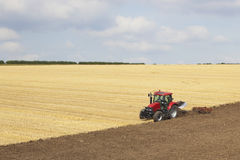 Red tractor plowing a field Stock Photography