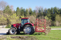 Red tractor for plowing on grass Royalty Free Stock Photo