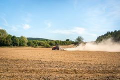 Tractor plows a field - agriculture and agronomy concept. Red tractor plows a field - agriculture and agronomy concept stock image