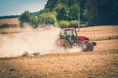 Tractor plows a field - agriculture and agronomy concept. Red tractor plows a field - agriculture and agronomy concept - retro style royalty free stock images