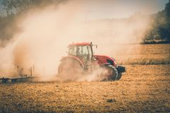 Tractor plows a field - agriculture and agronomy concept. Red tractor plows a field - agriculture and agronomy concept - retro style stock photos