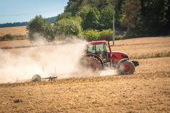 Tractor plows a field - agriculture and agronomy concept. Red tractor plows a field - agriculture and agronomy concept stock images