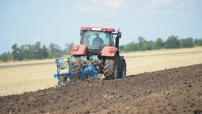 Red tractor plows the ground. Red tractor plows a field stock video footage
