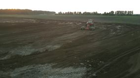 Red tractor plows field soil at sunset bird eye view. Little red tractor with plough plows field soil against green meadow at sunset bird eye view. Concept stock video
