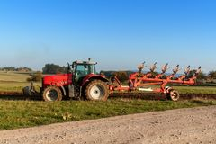 Red tractor pole field. Autumn field work. Life on the farm. Agricultural landscape in the Czech Republic. Royalty Free Stock Photos