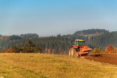 Red tractor pole field. Autumn field work. Life on the farm. Agricultural landscape in the Czech Republic. Stock Images