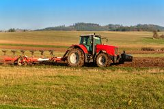 Red tractor pole field. Autumn field work. Life on the farm. Agricultural landscape in the Czech Republic. Royalty Free Stock Photography