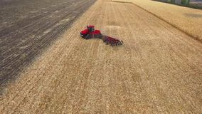 Red tractor preparing land for sowing. aerial shot stock footage