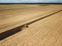 Red tractor preparing soil for sowing. Air view Royalty Free Stock Images