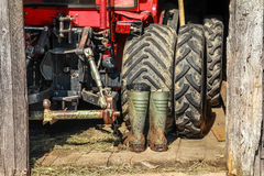 Red tractor and rubber boots in wooden barn Stock Photography
