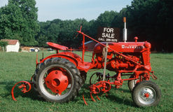 Red tractor with for sale sign Royalty Free Stock Images