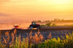 A red tractor with a seeder on a field  at sunset Royalty Free Stock Photo