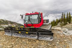 Red tractor, snow plough parked outside a mountain on the rocks stock images