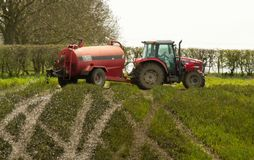 Red tractor spreading spreading slurry on fields Stock Photos