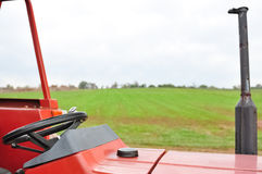 Red tractor  with steering wheel. Red tractor with steering wheel with green grass and sky in the background Royalty Free Stock Image