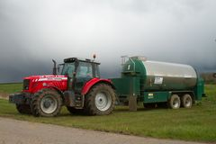 Red tractor and tanker in field. A modern massey ferguson tractor and tanker spreading fertilizer in crop field with black moody sky Royalty Free Stock Image