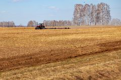 Red tractor with a trailed plow for mowing and weeding fields for the agro-industry of yellow color under the blue sky, a clear. Spring day. Preparation for stock images