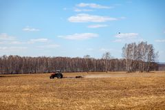 Red tractor with a trailed plow for mowing and weeding fields for the agro-industry of yellow color under the blue sky, a clear. Spring day. Preparation for royalty free stock photo