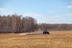 Red tractor with a trailed plow for mowing and weeding fields for the agro-industry of yellow color under the blue sky, a clear. Spring day. Preparation for stock photos